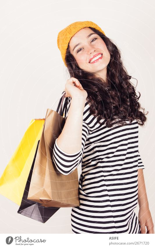Happy autumn or winter girl with wool cap shopping Shopping Beautiful Winter Woman Adults Autumn Dress Brunette Smiling Happiness Funny Yellow Black White bags