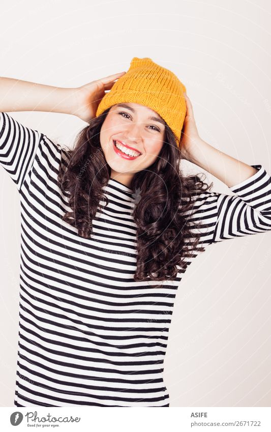 Happy autumn or winter girl with wool cap Beautiful Winter Woman Adults Autumn Dress Brunette Smiling Happiness Funny Yellow Black White Wool isolated ocher