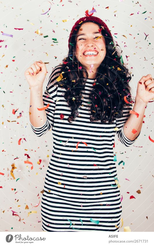 Laughing girl with striped dress and wool cap under a rain of confetti Joy Happy Beautiful Feasts & Celebrations Birthday Woman Adults Brunette Smiling Laughter