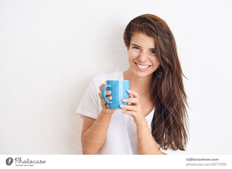 Smiling woman drinking coffee from blue mug Beverage Drinking Coffee Tea Happy Face Woman Adults 1 Human being 18 - 30 years Youth (Young adults) Scream