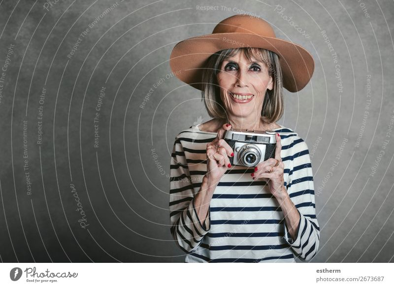 Portrait of Smiling senior woman with vintage photo camera on gray background Lifestyle Joy Leisure and hobbies Vacation & Travel Tourism Trip Adventure
