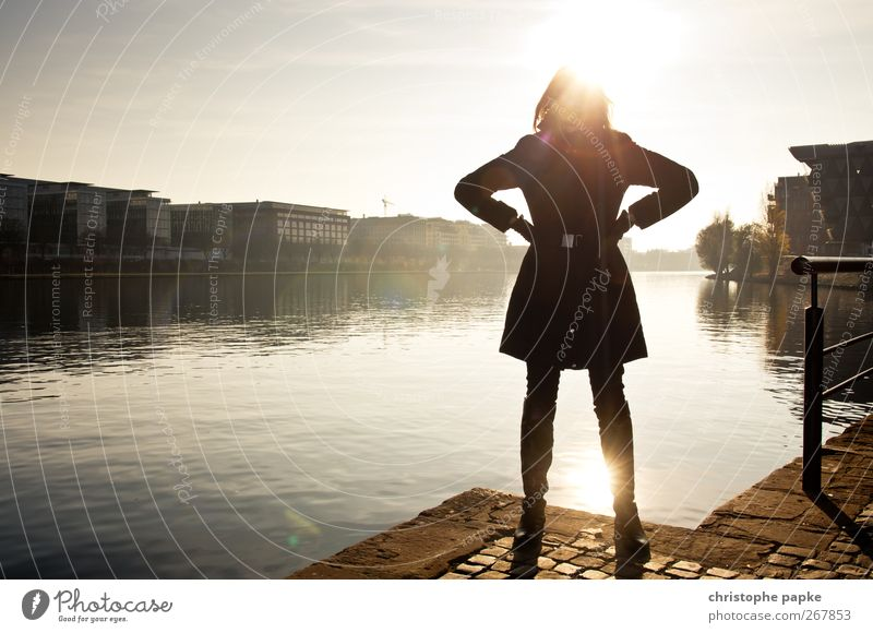 Human being Youth (Young adults) City Sun House (Residential Structure) Adults Feminine Autumn Wait Young woman 18 - 30 years Stand Illuminate Cool (slang) Jacket River bank