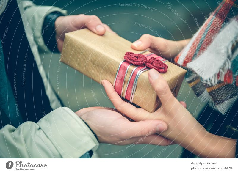 Man hands giving gift box to woman with scarf Lifestyle Happy Winter Feasts & Celebrations Birthday Human being Woman Adults Couple Hand Autumn Flower Street