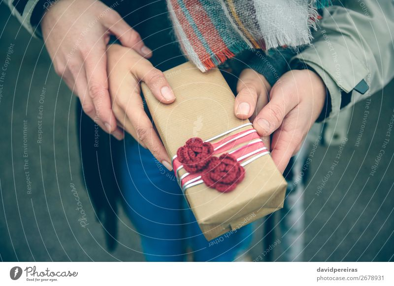 Woman and man hands showing gift box otdoors Lifestyle Happy Winter Feasts & Celebrations Birthday Human being Adults Man Couple Hand Autumn Flower Street Scarf
