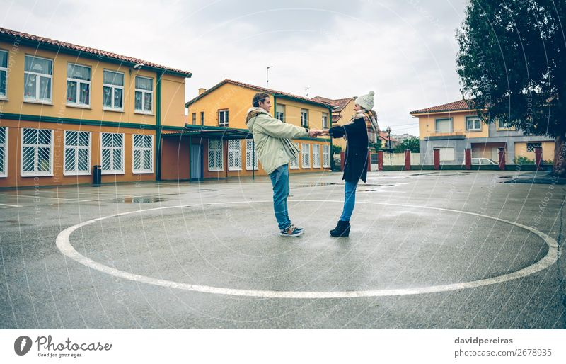 Couple holding hands inside of circle painted on floor Lifestyle Happy Beautiful Leisure and hobbies Winter Human being Woman Adults Man Friendship Arm Hand