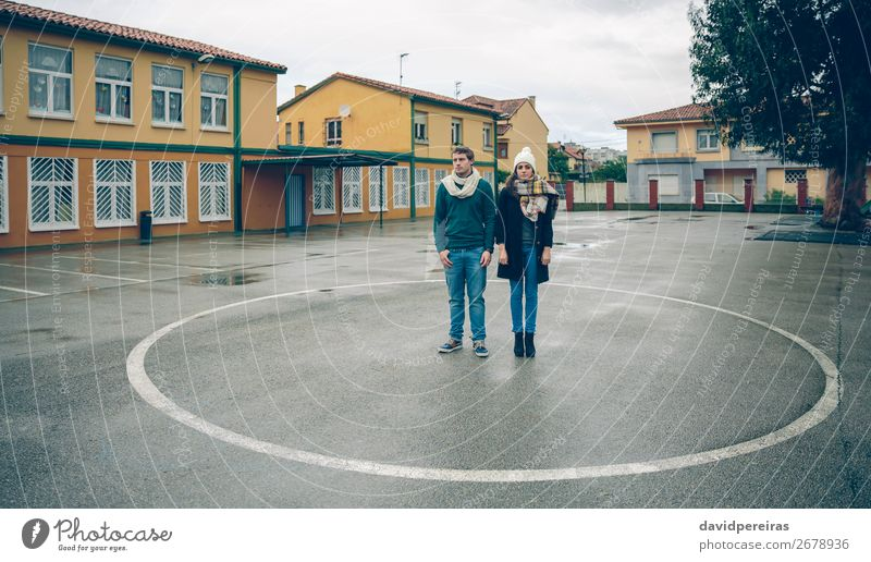 Couple standing inside of circle painted on floor Lifestyle Beautiful Leisure and hobbies Winter Human being Woman Adults Man Friendship Autumn Rain Street
