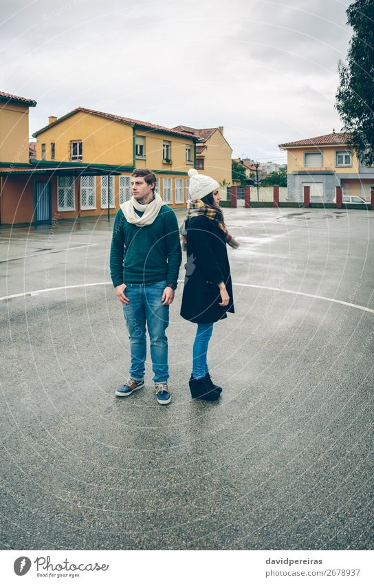Serious young couple wearing winter clothes standing outdoors Lifestyle Beautiful Relaxation Leisure and hobbies Winter Human being Woman Adults Man Friendship