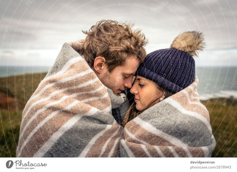 Young couple embracing outdoors under blanket in a cold day Lifestyle Beautiful Ocean Winter Mountain Woman Adults Man Couple Nature Sky Clouds Autumn Meadow