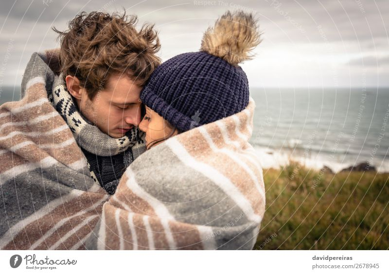 Young couple embracing outdoors under blanket in a cold day Lifestyle Happy Beautiful Ocean Winter Mountain Woman Adults Man Couple Nature Sky Clouds Autumn