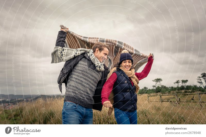 Young couple playing outdoors with blanket in a windy day Lifestyle Happy Beautiful Playing Ocean Winter Mountain Woman Adults Man Couple Nature Sky Clouds