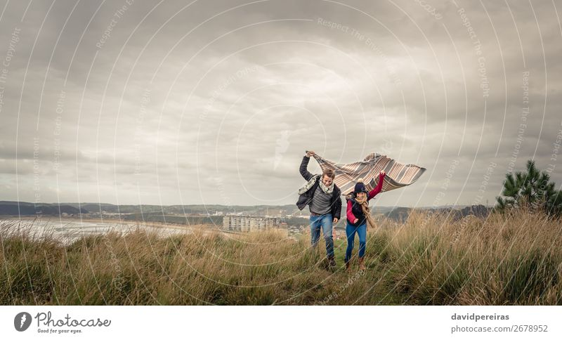 Young couple playing outdoors with blanket in a windy day Lifestyle Joy Happy Beautiful Playing Ocean Winter Mountain Woman Adults Man Couple Nature Sky Clouds