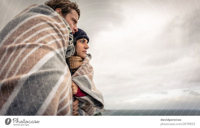 Young couple under blanket looking the sea in a cold day Lifestyle Happy Beautiful Ocean Winter Mountain Woman Adults Man Couple Nature Sky Clouds Autumn Wind