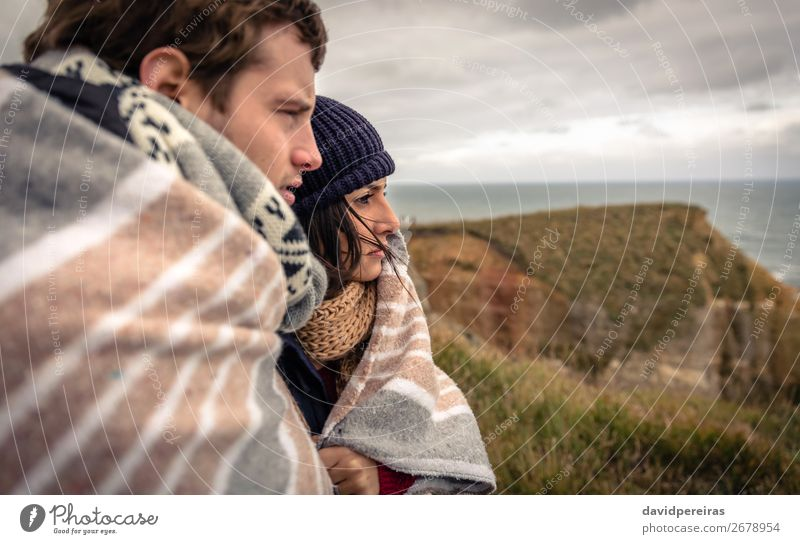 Young couple under blanket looking the sea in a cold day Lifestyle Beautiful Ocean Winter Woman Adults Man Couple Nature Sky Clouds Autumn Wind Meadow Coast