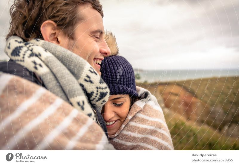 Young couple laughing outdoors under blanket in a cold day Lifestyle Happy Beautiful Ocean Winter Mountain Woman Adults Man Couple Nature Sky Clouds Autumn Wind