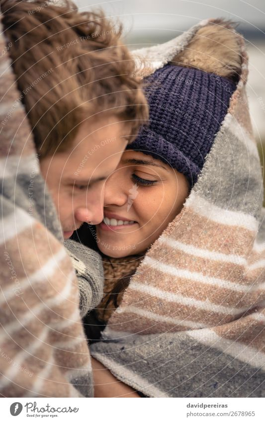 Young couple embracing outdoors under blanket in a cold day Lifestyle Happy Beautiful Winter Woman Adults Man Couple Nature Sky Clouds Autumn Wind Scarf Hat