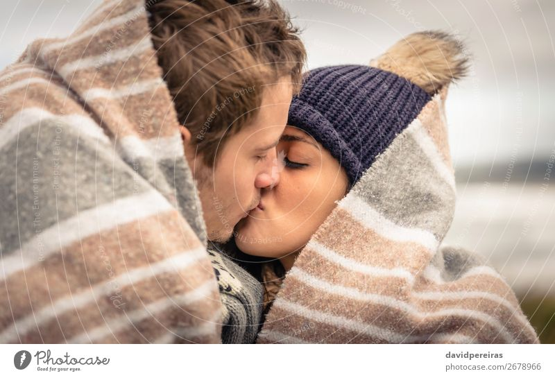 Young couple kissing outdoors under blanket in a cold day Lifestyle Happy Beautiful Ocean Winter Mountain Woman Adults Man Couple Nature Sky Clouds Autumn Wind