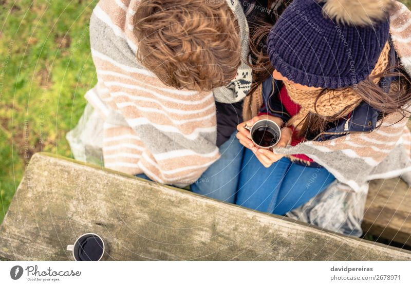 Young couple under blanket having hot drink in a cold day Beverage Coffee Tea Lifestyle Happy Winter Mountain Table Woman Adults Man Couple Hand Nature Autumn