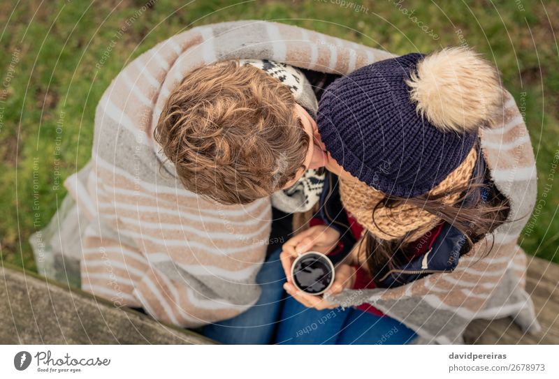Young couple under blanket with hot drink kissing outdoors Beverage Coffee Tea Lifestyle Adventure Winter Table Woman Adults Man Couple Hand Nature Autumn