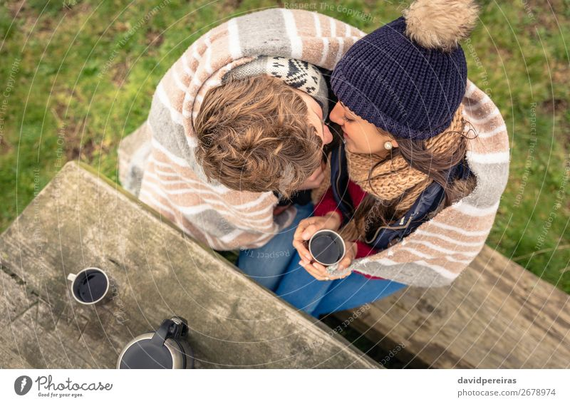 Young couple under blanket with hot drink kissing outdoors Beverage Coffee Tea Lifestyle Happy Winter Table Woman Adults Man Couple Hand Nature Autumn Wind