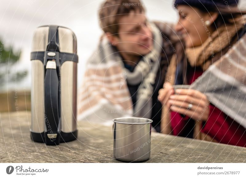 Metalic cup and thermos with couple on background Beverage Coffee Tea Lifestyle Happy Winter Table Woman Adults Man Couple Hand Nature Sky Clouds Autumn Wind