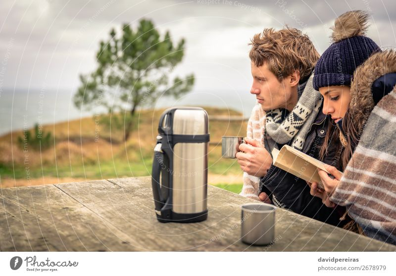 Young couple in a cold day with cloudy sky on the background Beverage Coffee Tea Lifestyle Happy Reading Ocean Winter Table Woman Adults Man Couple Hand Book