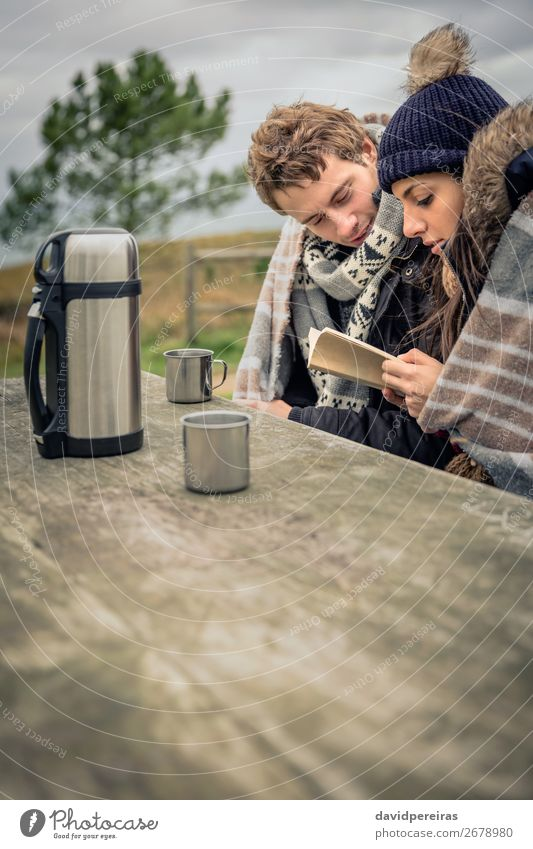 Young couple under blanket reading book outdoors in a cold day Beverage Coffee Tea Lifestyle Reading Adventure Winter Mountain Table Woman Adults Man Couple