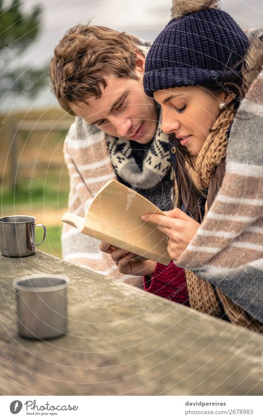 Young couple under blanket reading book outdoors in a cold day Beverage Coffee Tea Lifestyle Happy Reading Ocean Winter Mountain Table Woman Adults Man Couple