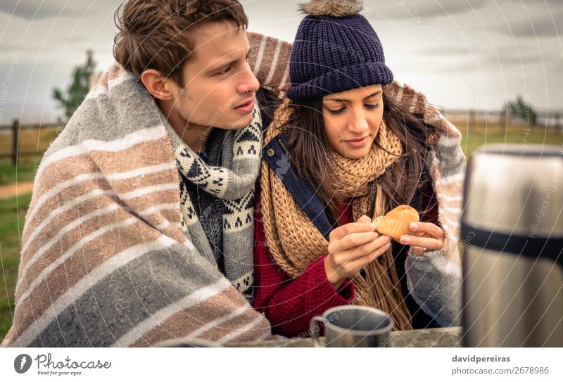 Young couple under blanket eating muffin outdoors in a cold day Eating Beverage Coffee Tea Lifestyle Happy Ocean Winter Table Woman Adults Man Couple Nature Sky
