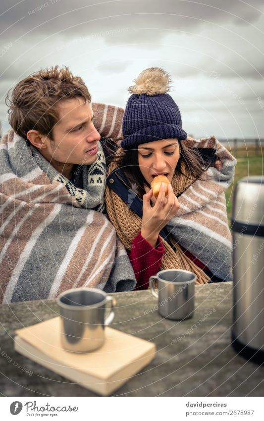 Young couple under blanket eating muffin outdoors in a cold day Eating Beverage Coffee Tea Lifestyle Adventure Ocean Winter Table Woman Adults Man Couple Nature