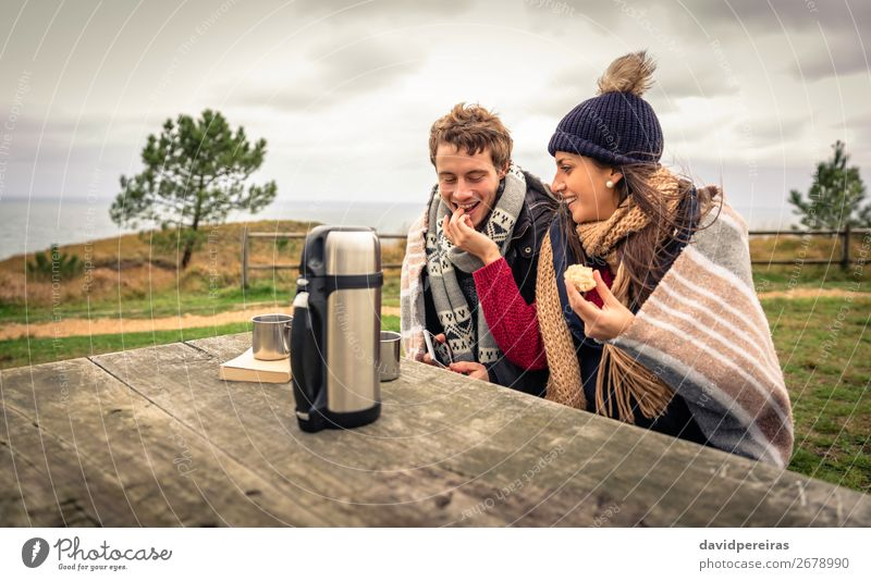 Young couple under blanket eating muffin outdoors in a cold day Eating Beverage Coffee Lifestyle Happy Ocean Winter Table Woman Adults Man Couple Nature Sky