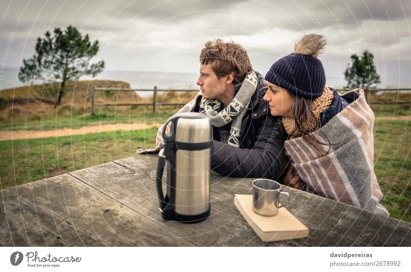 Young couple under blanket looking the sea in a cold day Beverage Coffee Tea Lifestyle Happy Ocean Winter Mountain Table Woman Adults Man Couple Nature Sky