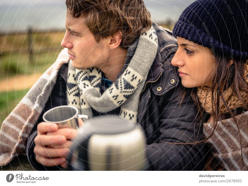 Young couple under blanket having hot drink in a cold day Beverage Coffee Tea Lifestyle Happy Winter Table Woman Adults Man Couple Hand Nature Sky Clouds Autumn