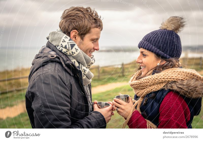 Young couple holding cups of hot drink outdoors in a cold day Beverage Coffee Tea Lifestyle Happy Ocean Winter Mountain Woman Adults Man Couple Hand Nature Sky