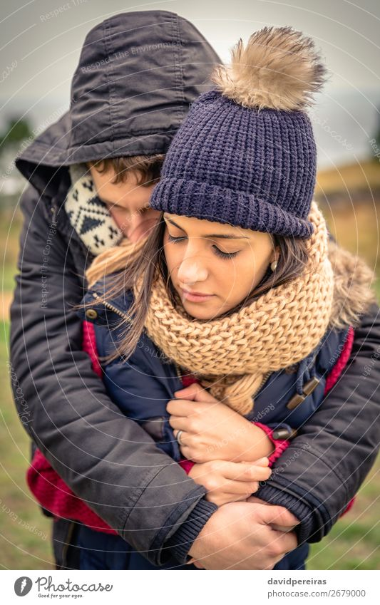 Young couple with hat and scarf embracing outdoors Lifestyle Happy Beautiful Winter Woman Adults Man Couple Nature Sky Clouds Autumn Wind Warmth Clothing Scarf