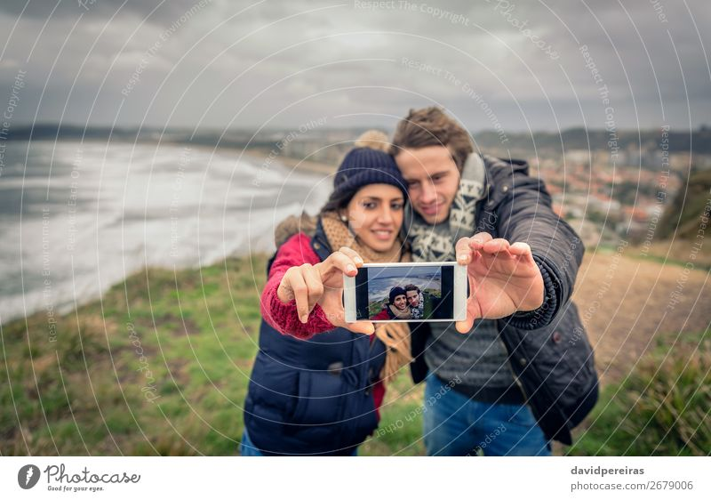 Young couple taking selfie photo with smartphone outdoors Woman Sky Nature Man Landscape Ocean Clouds Winter Beach Adults Autumn Love Meadow Coast Happy Couple