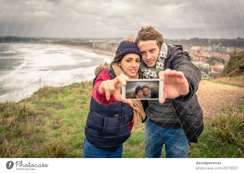 Young couple taking selfie photo with smartphone outdoors Lifestyle Happy Beach Ocean Winter Telephone PDA Camera Woman Adults Man Couple Nature Sky Clouds