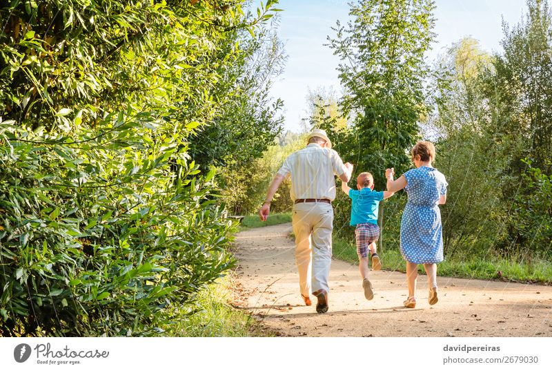Grandparents and grandchild jumping on nature path Lifestyle Joy Happy Leisure and hobbies Child Boy (child) Woman Adults Man Parents Grandfather Grandmother