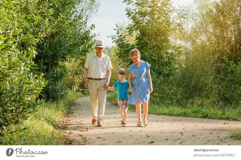 Grandparents and grandchild walking outdoors Happy Leisure and hobbies Summer Child To talk Human being Boy (child) Woman Adults Man Grandfather Grandmother