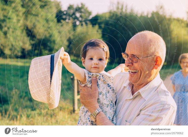 Baby girl playing with hat of senior man outdoors Woman Human being Nature Man Summer Relaxation Lifestyle Adults Love Family & Relations Laughter Happy Small