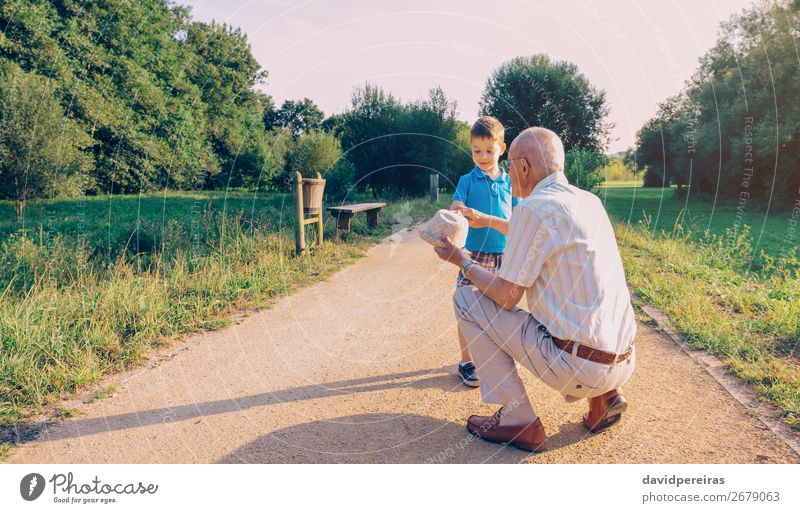 Grandfather showing his hat to grandchild outdoors Lifestyle Joy Happy Leisure and hobbies Playing Summer Child Boy (child) Man Adults Parents