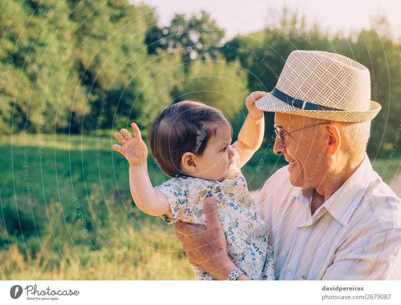 Baby girl playing with hat of senior man outdoors Lifestyle Happy Relaxation Playing Summer Human being Toddler Woman Adults Man Parents Grandfather