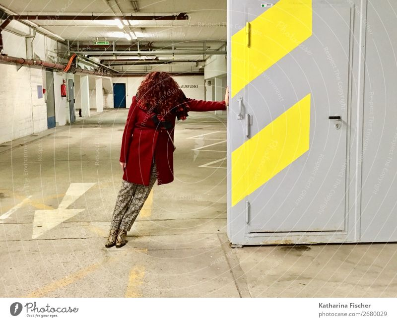Red-haired woman is standing in an underground car park. Feminine 1 Human being Pants Coat Scarf Footwear Curl Line Stand Brown Yellow Gray White