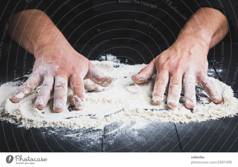 white wheat flour on a black wooden table Dough Baked goods Bread Table Kitchen Cook Human being Man Adults Hand Wood Make Dark Black White Flour chef Pizza