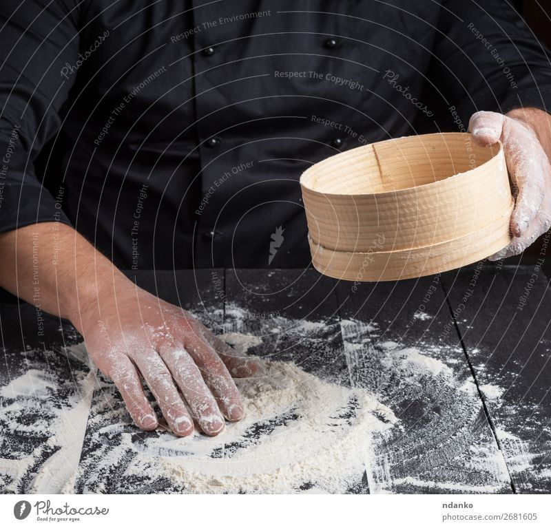 Chef prepares the dough of white flour Dough Baked goods Bread Nutrition Table Kitchen Cook Man Adults Hand Sieve Wood Dark Natural White Flour cooking food