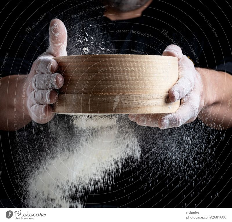 man sifts white wheat flour through a wooden sieve Dough Baked goods Bread Nutrition Kitchen Cook Human being Man Adults Hand Sieve Movement Make Fresh Black