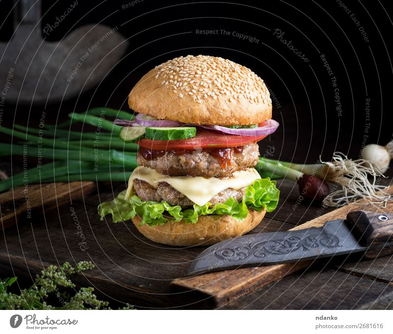 cheeseburger with vegetables Meat Cheese Vegetable Bread Roll Lunch Dinner Fast food Knives Table Restaurant Wood Dark Fresh Large Delicious Green Red Black