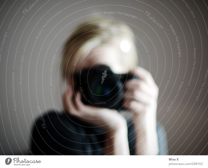 postural mark Human being 1 Blonde To hold on Photography Photographer Take a photo Camera Colour photo Subdued colour Reflection Blur Looking into the camera