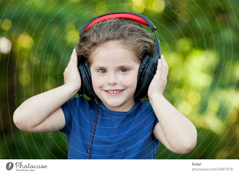 Little girl with headphones outside Lifestyle Joy Happy Beautiful Leisure and hobbies Playing Summer Music Child Technology Human being Woman Adults Infancy