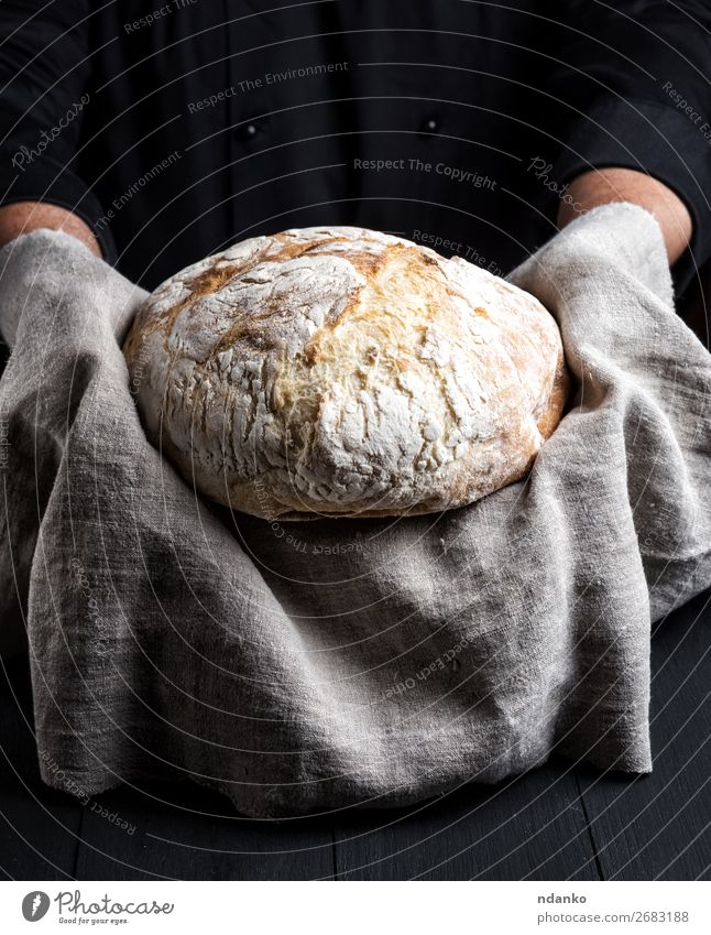 baked round homemade bread on a gray napkin Bread Nutrition Table Kitchen Cook Human being Hand Wood Eating Make Dark Fresh Brown Black White Tradition Baking