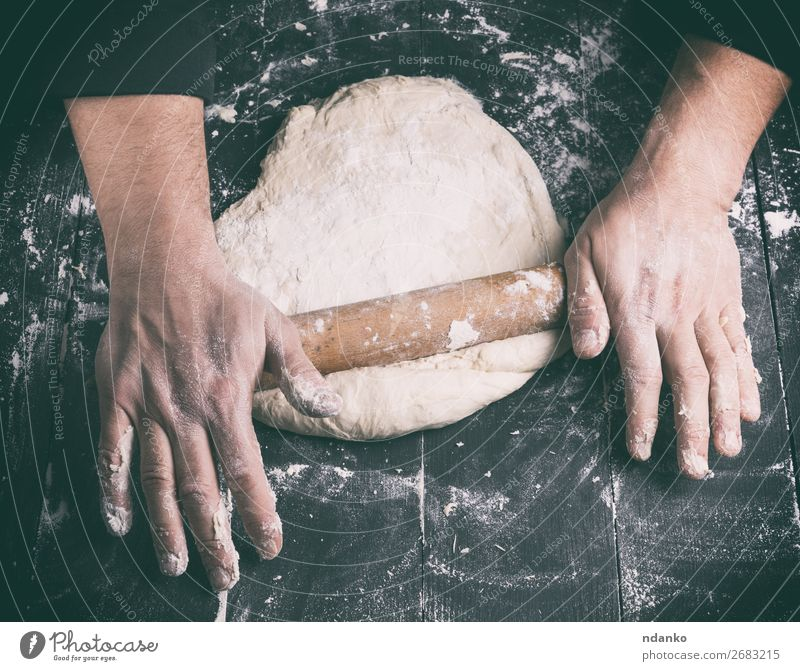 chef in a black tunic rolls a dough for a round pizza Dough Baked goods Bread Nutrition Table Kitchen Human being Man Adults Hand Wood Make Fresh Black White